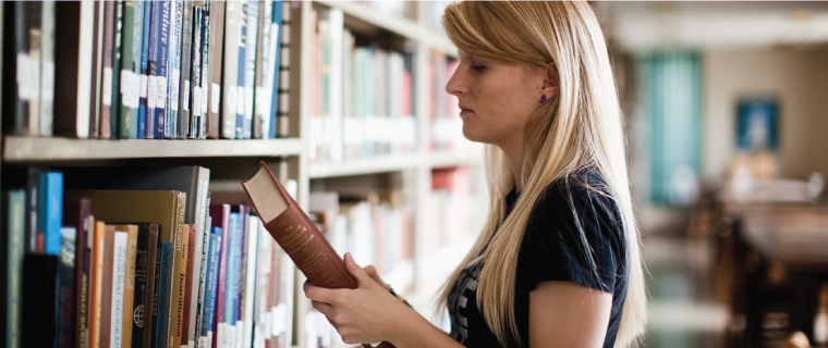 Student doing research in the library, holding a book