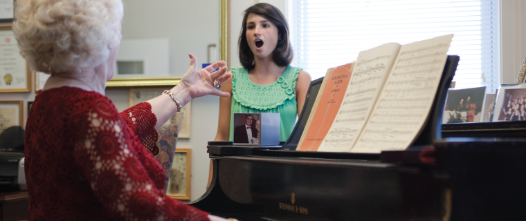 Dr. Betty Campbell directing a student while playing the piano