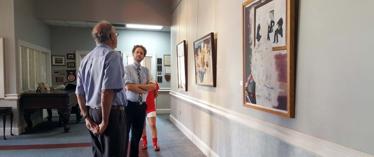 "Artist Nicholas Tisdale (right) speaks with Dr. Thomas Wilson (left) at the opening reception for ""Excised""."